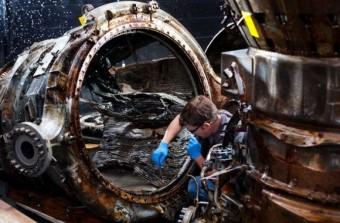 Uno dei restauratori sta usando una spazzola per pulire una camera di spinta del motore F-1