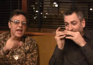 """Alan Sorrenti e Angelo Adamo improvvisano un inedito """"Figli delle stelle"""" per voce e armonica solo (fotogramma dall'intervista video)."""