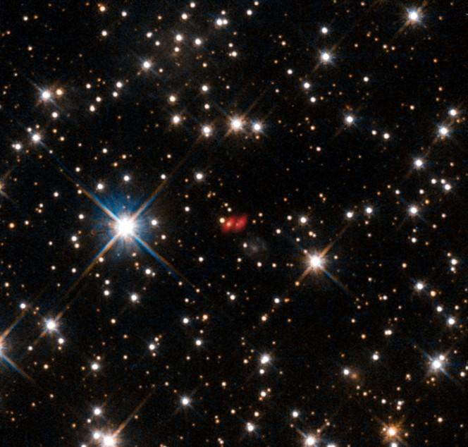 Questa immagine dal Telescopio Spaziale Hubble della NASA/ESA mostra la galassia attiva distante PKS 1830-211, difficile da identificare tra la vere stelle, molto più vicine. Recenti osservazioni con ALMA mostrano entrambe le componenti di questa lontana lente gravitazionale e sono segnate in rosso in questa immagine composita. (Crediti: ALMA (ESO/NAOJ/NRAO)/NASA/ESA/I. Martí-Vidal)