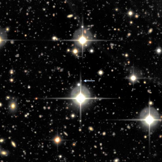 Una piccola porzione della Supernova Legacy Survey. Si vede SNLS-06D4eu e la sua galassia ospite (freccia): sono così distanti che entrambi sono un minuscolo punto di luce che non può essere chiaramente differenziato in questa immagine. I grandi oggetti luminosi, con punte sono stelle nella nostra galassia. Ogni altro punto di luce è una galassia lontana. (Crediti: Immagine per gentile concessione della University of California - Santa Barbara)