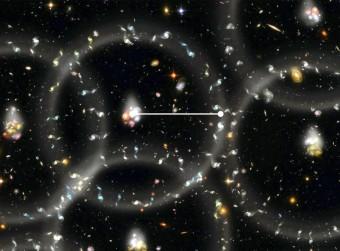 """Rappresentazione artistica della misurazione della scala di misura dell'universo. Le oscillazioni acustiche dei barioni si riflettono nella tendenza (molto esagerata nell'illustrazione) di galassie e altri corpi a raggrupparsi in sfere. Sfere che in origine erano onde di densità in propagazione nel plasma dell'universo primordiale. Il raggio delle sfere (linea bianca) rappresenta la scala di un """"righello standard"""" che permette agli astronomi di determinare, con la precisione dell'uno per cento, la struttura a larga scala dell'universo. Crediti: Zosia Rostomian/LBNL."""