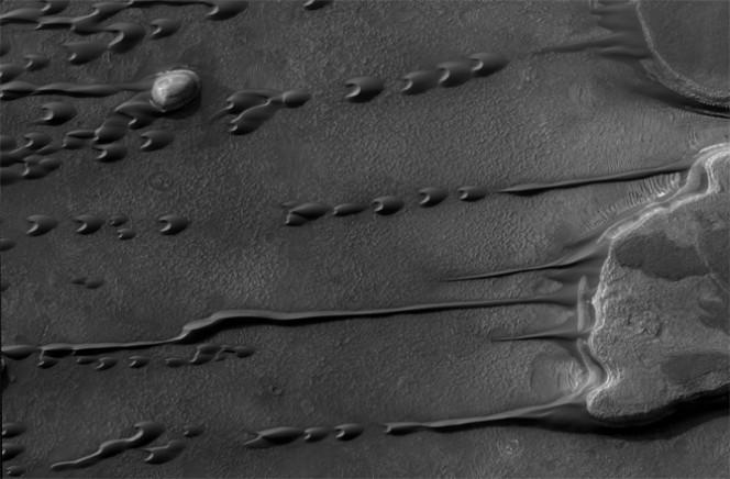 Le stesse dune viste da più in alto. In questa immagine si nota che il vento sta erodendo delle piccole colline a destra della foto, portando il materiale verso sinistra e creando piccole dune barcane. Crediti: NASA/JPL-CALTECH/UNIVERSITY OF ARIZONA