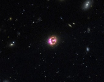 Le immagini multiple di un quasar distante sono visibili in questa combinazione di riprese ottenute dai telescopi orbitanti Chandra e Hubble della NASA. I dati raccolti da Chandra sono stati utilizzati per misurare in modo diretto la velocità di rotazione del buco nero supermassiccio che alimenta l'emissione di energia del quasar. Crediti:  NASA/CXC/Univ of Michigan/R.C.Reis et al. Nella banda della luce visibile: NASA/STScI