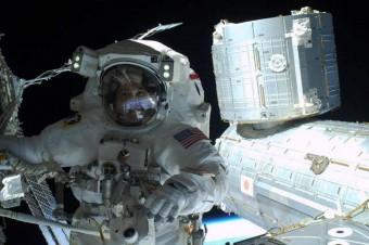 L'astronauta della NASA Steve Swanson posa per la fotocamera di Rick Mastrangelo durante la passeggiata spaziale del 23 aprile 2014. Sullo sfondo: il laboratorio giapponese Kibo della Stazione Spaziale Internazionale e il pianeta Terra.