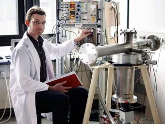 Nils Haag con lo strumento che gli ha permesso di determinare lo spettro degli antineutrini prodotti dalla fissione dell'uranio 238. Crediti: Wenzel Schuermann / TU München