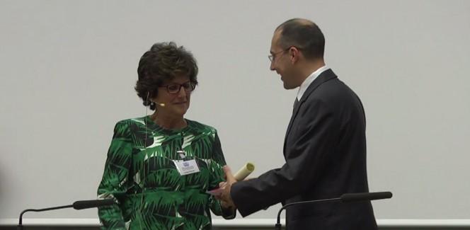 Il presidente SIF Luisa Cifarelli consegna il premio Bassoli per l'outreach a Marco Galliani di INAF, durante la cerimonia di apertura del 100° congresso nazionale.