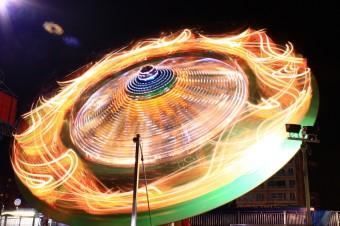Le scie luminose di una giostra possono rendere l'idea della complessità dello spiraleggiare di due buchi neri prima di fondersi