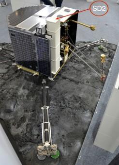 Un modellino del lander Philae. La freccia indica lo strumento SD2, il trapano entrato in azione oggi. Crediti: ESA