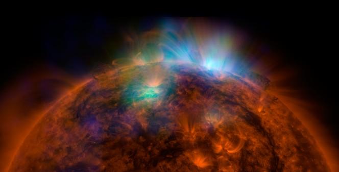 Alla ripresa del disco e della bassa atmosfera solare ottenuta dal Solar Dynamics Observatory della NASA nell'ultravioletto (in rosso-arancio) sono sovrapposte quelle di NuSTAR in verde e blu che ci svelano la radiazione di alta energia emessa dalla nostra stella.  Crediti: NASA/JPL-Caltech/GSFC