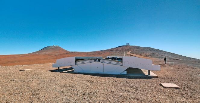 Questa immagine mostra la cupola dell'NGTS durante il giorno. Le cupole di VISTA (a destra) e del VLT (a sinistra) spuntano all'orizzonte. Crediti: ESO/R. Wesson