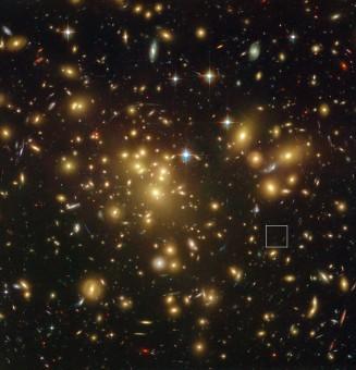 L'immagine del telescopio spaziale Hubble della NASA/ESA mostra il ricco ammasso di galassie Abell 1689. L'enorme concentrazione di massa deflette la luce proveniente dagli oggetti più lontani e può aumentarne la luminosità apparente e renderle osservabili. Uno di questi oggetti, A1689-zD1, si trova all'interno del riquadro - anche se è ancora così debole che si vede appena in questa immagine. Crediti: NASA; ESA; L. Bradley (Johns Hopkins University); R. Bouwens (University of California, Santa Cruz); H. Ford (Johns Hopkins University); and G. Illingworth (University of California, Santa Cruz)