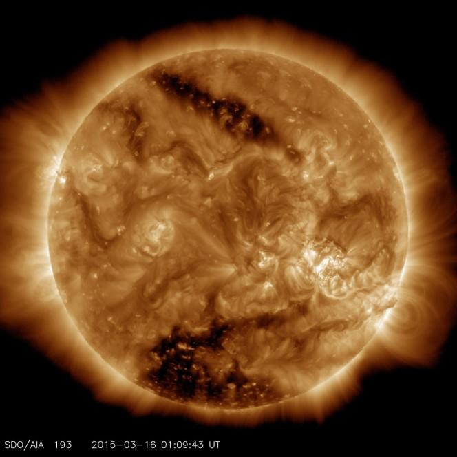 Le due zone scure presenti in questa immagine, catturata dal Solar Dynamics Observatory della NASA lo scorso 16 marzo, mostrano due buchi coronali molto estesi. Quello che si trova nella parte bassa è uno dei più grandi mai osservati in decenni. Crediti: NASA/SDO