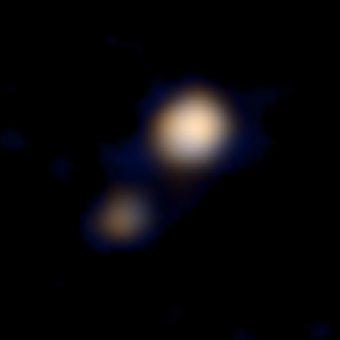 "Prima immagine a colori di Plutone e Caronte ripresa dalla sonda New Horizons con la camera ""Ralph"" il 9 aprile 2015 da una distanza di circa 115 milioni di chilometri. Crediti: NASA/Johns Hopkins University Applied Physics Laboratory/Southwest Research Institute"
