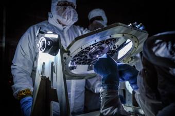 Ingegneri NASA ispezionano un Micro Shutter Array, un dispositivo sviluppato per il James Webb Space Telescope, durante una fase di collaudo. I Micro Shutter Array, che verranno utilizzati nello spettrometro nel vicino infrarosso (NIRSpec), sono matrici di circa 62.000 micro-sportelli (ciascuno di dimensioni di 200 micron) che possono essere aperti a comando nella configurazione desiderata dall'astronomo, permettendo di ottenere spettri di qualche centinaio di oggetti astronomici simultaneamente. Crediti: NASA Goddard/Chris Gunn