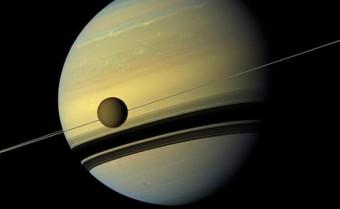 Una vista in colori naturali della luna Titano di fronte a Giove ottenuta dalla sonda Cassini. Crediti: NASA/JPL-Caltech/SSI