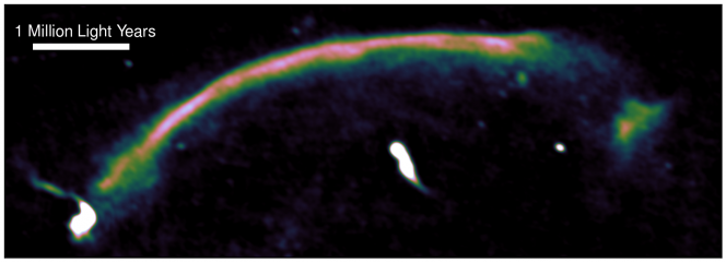 """Un'immagine radio mette in evidenza l'onda d'urto all'interno dell'ammasso """"salsiccia"""", che appare come un arco luminoso che va da in basso a sinistra in alto a destra. L'immagine è stata realizzata utilizzando il Giant Metrewave Radio Telescope. L'onda d'urto è stata generata un miliardo anni fa, quando i due ammassi originali si sono fusi, e si muove alla velocità molto elevata di 9 milioni di km/h. Crediti: Andra Stroe"""