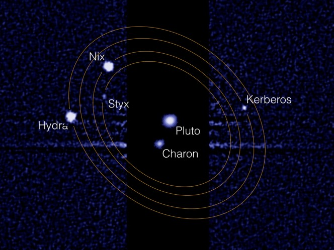 """Questa immagine composita ottenuta dallo Hubble Space Telescope mostra Plutone e la sua luna maggiore Caronte al centro. A destra e sinistra si possono scorgere le quattro lune minori che orbitano questa sorta di """"pianeta binario"""". Essendo estremamente meno luminose, le quattro lune hanno richiesto un tempo di esposizione 1000 volte superiore rispetto alla coppia centrale. Crediti: NASA, ESA, Mark Showalter (SETI Institute)"""