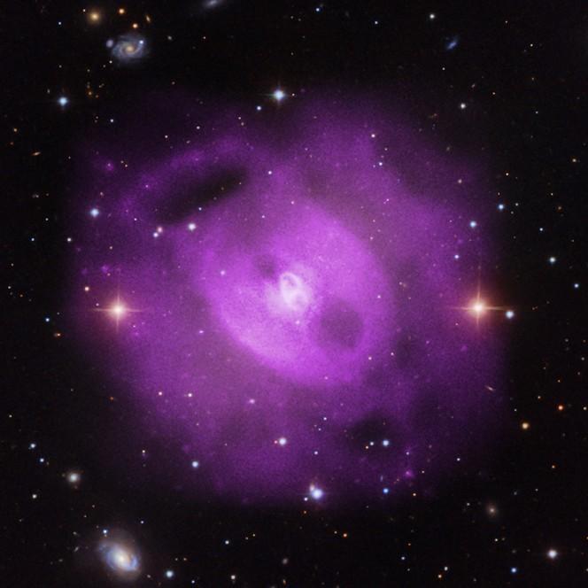 Immagine composita del gruppo di galassie NGC 5813. In violetto le riprese nei raggi X del telescopio spaziale Chandra della NASA che mettono in evidenza tre coppie di cavità nel gas caldo che permea questo oggetto celeste. Crediti:  Nei raggi X, NASA/CXC/SAO/S.Randall et al., Nell'ottico,  SDSS