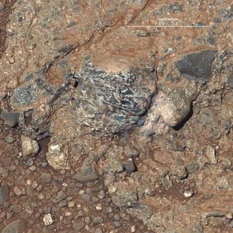 Un frammento di roccia ignea incastonato in un conglomerato roccioso presso il cratere Gale, su Marte, mostra feldspati di colore chiaro in forma di cristalli allungati. Sarebbero la traccia della crosta continentale marziana. Crediti: NASA / JPL-Caltech / LANL / IRAP / U. Nantes / IAS / MSSS.