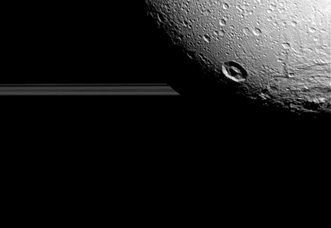 Qui Dione vista da 158mila km di distanza, con i crateri in primo piano – esaltati dal contrasto fra luci e ombre – e gli anelli di Saturno sullo sfondo. La risoluzione è di circa 950 metri per pixel. Crediti: NASA / JPL-Caltech / Space Science Institute