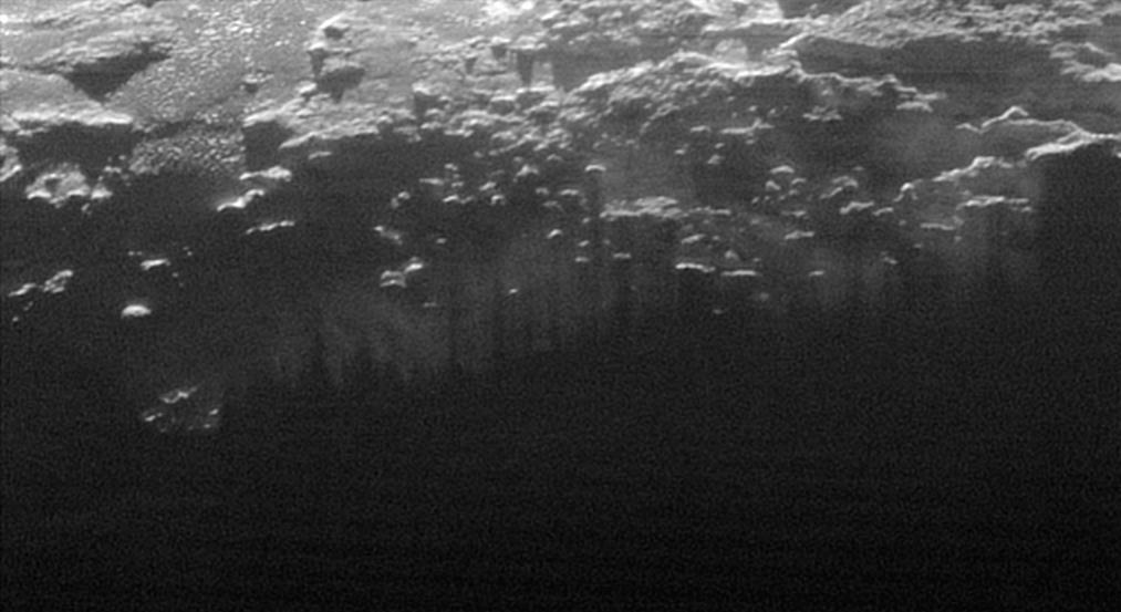 Il sole al tramonto illumina la foschia che ricopre la superficie di Plutone, tagliata dalle ombre delle molte colline e piccole montagne. Credit: NASA/Johns Hopkins University Applied Physics Laboratory/Southwest Research Institute