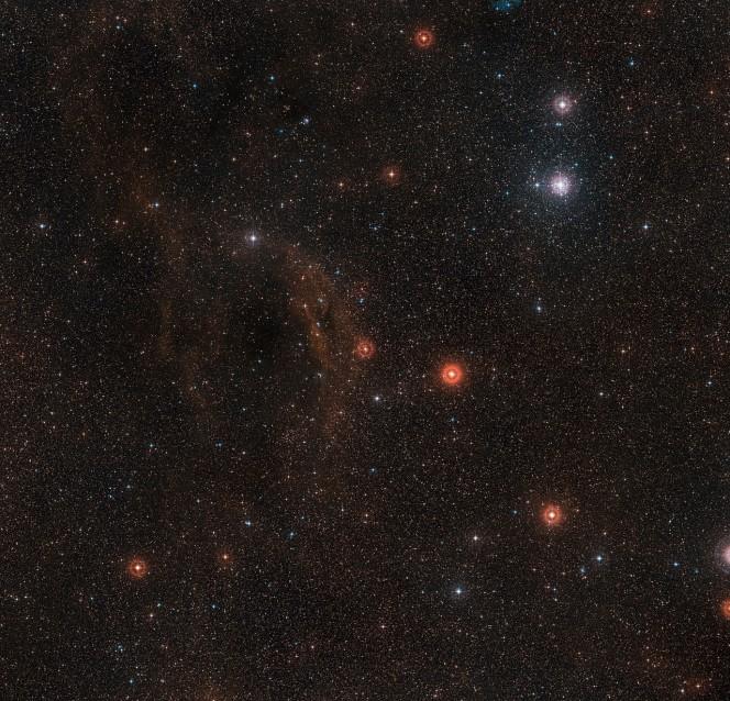 Questa panoramica mostra il cielo intorno alla brillante ipergigante rossa VY Canis Majoris, una delle stelle più grandi nota nella Via Lattea. La stella stessa è al centro dell'immagine, che comprende anche nubi di idrogeno gassoso incandescente, nubi di polvere e l'ammasso stellare che circonda la stella luminosa Tau Canis Majoris, in alto a destra. Questa immagine è stata ottenuta a partire da dati della DSS2 (Digitized Sky Survey 2). Crediti: ESO/Digitized Sky Survey 2. Acknowledgement: Davide De Martin