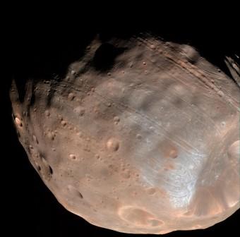 Un nuovo modello suggerisce che le scanalature che attraversano la luna di Marte Phobos siano state prodotte dall'attrazione gravitazionale reciproca fra il pianeta e il suo satellite. Crediti: NASA / JPL-Caltech / Università dell'Arizona.