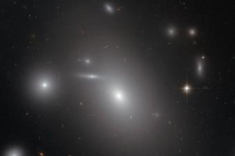 Questa immagine mostra la galassia ellittica NGC 4889 in primo piano rispetto a centinaia di galassie sullo sfondo. Al centro della galassia, ben nascosto all'occhio umano, c'è un buco nero supermassiccio gigantesco: contiene la bellezza di 21 miliardi di soli. Crediti: NASA e ESA