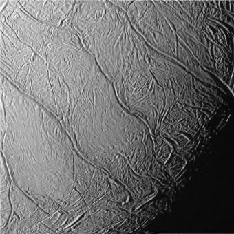 """Nell'immagine un primo piano della superficie di Encelado, dove è possibile apprezzare le fratture che ricoprono la sua superficie e che sono state chiamate in maniera informale """"strisce di tigre"""" a causa della loro forma allungata e più o meno parallela. A partire da queste fenditure partono i geyser di lunga durata di Encelado. Crediti: NASA/JPL/Space Science Institute"""