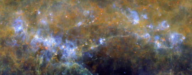 Figura 1: Una vista profonda nell'infrarosso al complesso RCW106, una regione gigante nel Piano Galattico dell'emisfero sud. Estendendosi per più di un grado nel cielo il Complesso Molecolare Gigante RCW 106 include parecchie regioni brillanti di idrogeno ionizzato HII e nubi di formazione stellare di alta massa circondate da materia diffusa. Le zone più brillanti dell'immagine individuano le regioni dove la polvere, che oscura la luce visibile, è scaldata dalle stelle appena nate: le regioni che le circondano, quindi, sono più calde e mostrano una colorazione più blu, mentre la materia diffusa più fredda risulta più rossa. Nell'immagine è chiaramente visibile una grande varietà di strutture filamentos: le strutture ad arco sono prodotte dall'interazione del campo di radiazione e dai venti delle stelle appena formate con la nube stessa da cui sono nate. Questo complesso è situato nel braccio Scudo-Croce della Via Lattea, a una distanza di 3.6 kiloparsec dal Sole ed è composto da 6 distinte regioni allineate parallelamente al Piano Galattico. La regione più ad Est (la più a sinistra nell'immagine) è G333.6-0.2, una delle più brillanti regioni del cielo infrarosso, con una luminosità totale di 3 milioni di volte il Sole, dovuta all'eccitazione, da parte di un ammasso stellare compatto contenente almeno una dozzina di giovani stelle di tipo O/B, non visibili in questa immagine infrarossa.