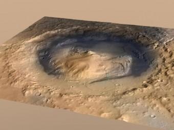 Visuale d'insieme del cratere Gale, il punto di atterraggio del rover Curiosity su Marte. All'interno del cratere è presente un rilievo alto 5.5 mila km che si chiama Monte Sharp. Il cerchio indica il punto d'approdo di Curiosity, la linea blu rappresenta il suo tragitto. Crediti: NASA/JPL