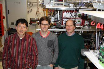 Da sinistra a destra: il professor Kilian Singer, a capo del progetto, il dottorando Johannes Roßnagel, e il professor Ferdinand Schmidt-Kaler, a capo del team QUANTUM. I tre co-autori dello studio posano davanti dell'apparecchiatura sperimentale utilizzata per creare il motore atomico presso l'Università di Mainz. Crediti: AG QUANTUM