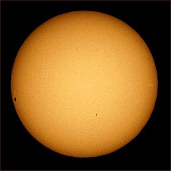 Immagine raccolta durante il transito di Mercurio dell'8 novembre 2006. Si noti che la macchia solare vicina all'equatore a sinistra è molto più grande di Mercurio, che si trova invece verso il centro, in basso a destra. Crediti: Wikipedia