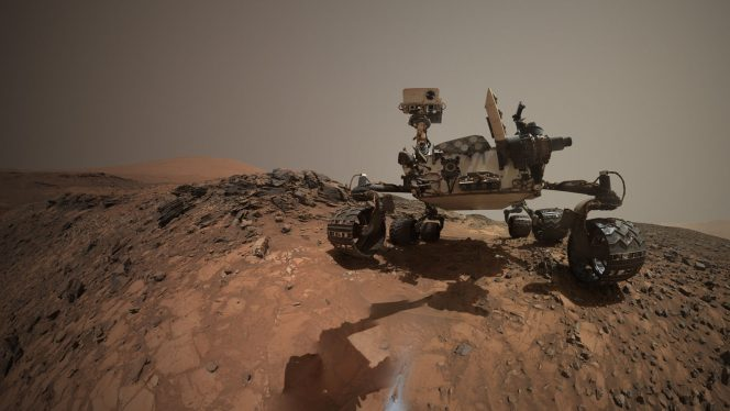 Il selfie del rover NASA Curiosity, sul sito marziano dove è stato raccolto un campione della roccia chiamata Buckskin. Circondata da un ciuffo di polvere iridescente, la foratura nel suolo marziano è ben visibile in primo piano. Crediti: Crediti: NASA / JPL-Caltech / MSSS.