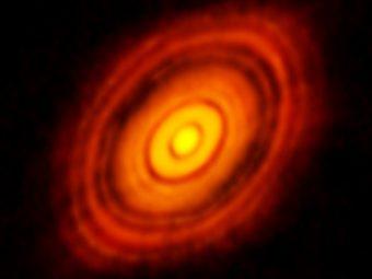 Questa immagine ottenuta dal radiotelescopio ALMA mostra il disco protoplanetario che circonda la giovane stella HL Tauri. Sono individuabili anche le posizioni di possibili pianeti, in formazione nelle macchie scure all'interno del sistema. Crediti: ALMA (ESO/NAOJ/NRAO)