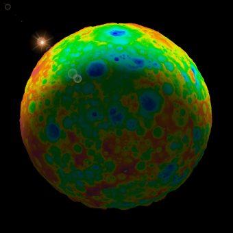 """In quest'immagine, il più grande fra i crateri da impatto meglio preservati di Cerere, Kerwan (280 km), visto di lato, vicino all'estremità superiore. I differenti colori indicano l'elevazione (bassa in blu, alta in rosso) amplificata di un fattore 3. Kerwan degrada gradualmente, verso il terminatore (la zona in ombra), in una depressione profonda 4 km e dal diametro di 800 km, probabile """"relitto"""" d'un impatto avvenuto agli albori della storia collisionale. Crediti: Southwest Research Institute/Simone Marchi"""