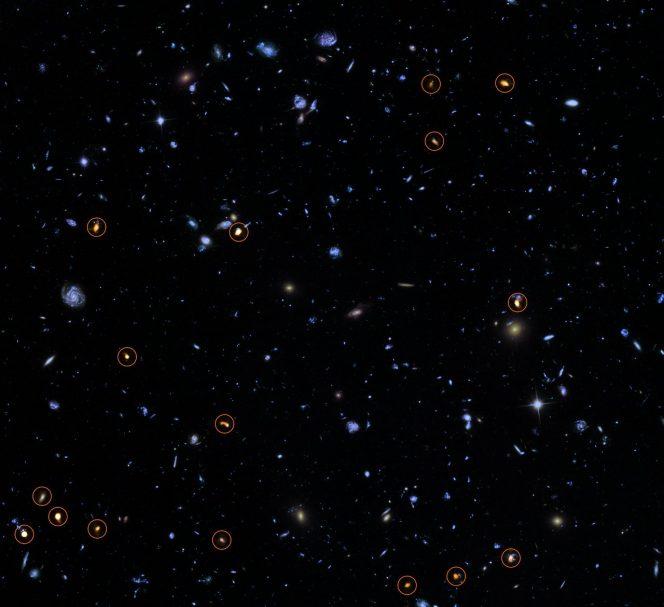 Questa immagine combina una fotografia presa dal telescopio spaziale Hubble della NASA/ESA, sullo sfondo, con una veduta recentissima e molto profonda di ALMA (in arancione, indicata da cerchi). Tutti gli oggetti visti da ALMA sono galassie con un alto tasso di formazione stellare. L'immagine si basa sulla survey ALMA di J. Dunlop e colleghi, che copre l'intero campo HUDF. Crediti: ALMA (ESO/NAOJ/NRAO)/NASA/ESA/J. Dunlop et al. and S. Beckwith (STScI) and the HUDF Team