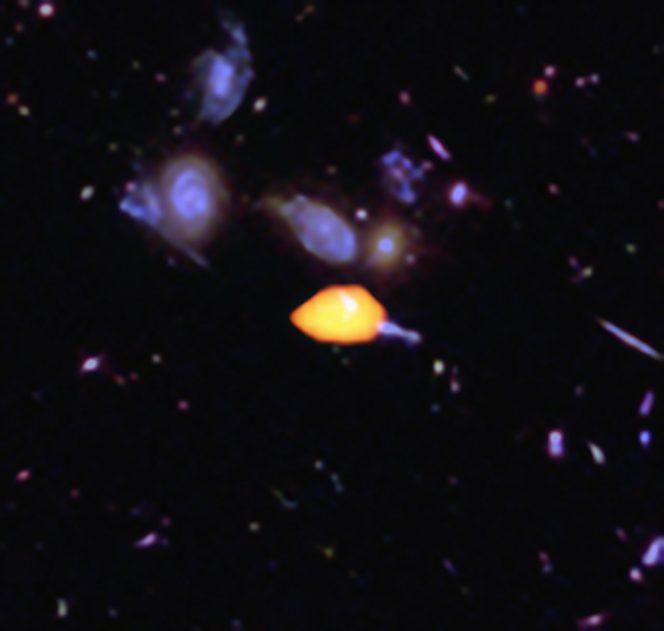 ALMA ha osservato il Campo Ultra-profondo di Hubble scoprendo nuovi dettagli della storia di formazione stellare dell'Universo. Questa immagine mostra una di queste galassie in primo piano (in arancione): è ricca di monossido di carbonio, perciò è pronta per la formazione stellare. Le strutture blu sono immagini di galassie viste da Hubble. L'immagine si basa sulla survey molto profonda ottenuta con ALMA di Manuel Aravena, Fabian Walter e colleghi, che copre circa un sesto dell'intera area dell'HUDF. Crediti: B. Saxton (NRAO/AUI/NSF); ALMA (ESO/NAOJ/NRAO); NASA/ESA Hubble