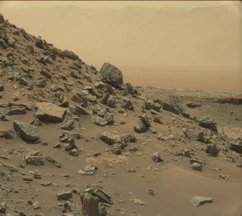 Nell'immagine ripresa dalla Mast Camera a bordo di Curiosity, un pendio inclinato nellaregione chiamata Murray Buttes, alla base del Monte Sharp. In lontananza, sebbene offuscato dalla foschia polverosa, è visibile il bordo del cratere Gale, dove il rover è arrivato nel 2012. Crediti: NASA/JPL-Caltech/MSSS