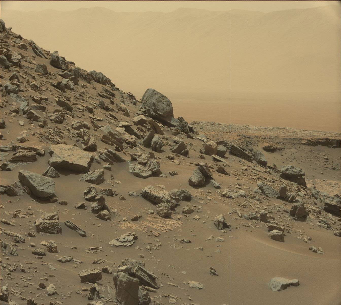 Nell'immagine ripresa dalla Mast Camera a bordo di Curiosity, un pendio inclinato nella regione chiamata Murray Buttes, alla base del Monte Sharp. In lontananza, sebbene offuscato dalla foschia polverosa, è visibile il bordo del cratere Gale, dove il rover è arrivato nel 2012. Crediti: NASA/JPL-Caltech/MSSS