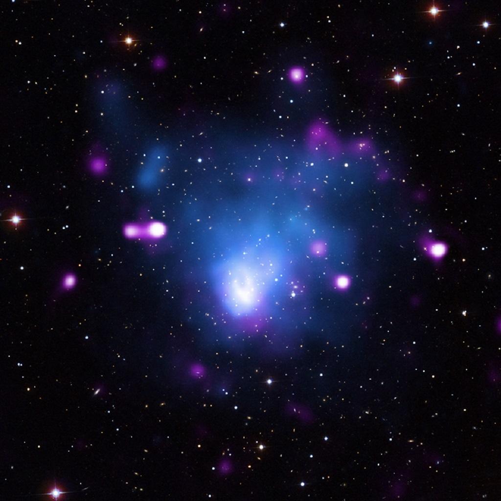 Questo sistema, noto come Abell 665, mostra un'onda d'urto estremamente potente. Qui, i raggi X colti da Chandra (in blu) mostrano il gas caldo nel cluster. Ai dati di Chandra sono stati aggiunti quelli sull'emissione radio (in viola) e i dati della luce visibile dalla Sloan Digital Sky Survey che mostra le galassie e le stelle (in bianco). Crediti: X-ray: NASA/CXC/Univ. of Alabama/S.Dasadia et al, Radio: NSF/NRAO/VLA, Optical: SDSS