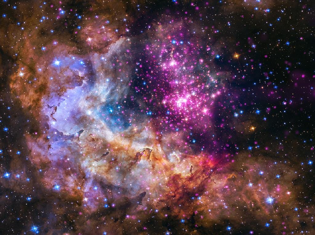 Il giovane ammasso Westerlund 2 a 20 mila anni luce dalla Terra. I dati in luce visibile vengono da Hubble (verde e blu), i dati a raggi X in viola vengono da Chandra. Crediti: X-ray: NASA/CXC/SAO/Sejong Univ./Hur et al; ; Optical: NASA/STScI