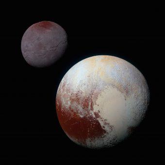 """Plutone, in primo piano in questa immagine in falsi colori, ha un """"cuore"""" di ghiaccio sulla propria superficie. E' individuabile nella foto il lobo a sinistra, quello meno ovale che corrisponde al bacino denominato provvisoriamente Sputnik Planitia. In secondo piano la luna di Plutone, Caronte. Crediti: NASA/JHUAPL/SWRI"""