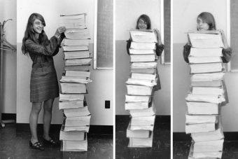 Margaret Hamilton accanto alla pila di volumi di software prodotto da lei e dal suo team del MIT per il Programma Apollo. Crediti: Wikimedia Commons